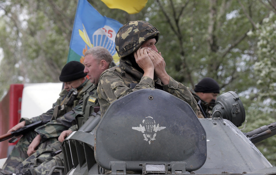 Photo - Ukrainian army paratroopers move to position in Slovyansk, Ukraine, Monday, June 2, 2014. Hundreds of armed insurgents attacked a border guards' camp in eastern Ukraine Monday, as rebels nearby promised safety for the officers if they surrendered the base and lay down their arms. (AP Photo/Efrem Lukatsky)