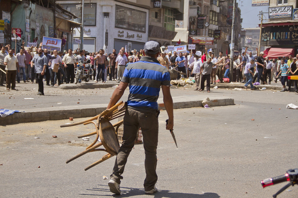 An Egyptian opposition protester holds a chair and knife during a clash between supporters and opponents of President Mohammed Morsi in downtown Damietta, Egypt, Wednesday, July 3, 2013. The deadline on the military's ultimatum to President Mohammed Morsi has expired, with 48 hours passing since the time it was issued. Giant cheering crowds of Morsi's opponents have been gathered in Cairo's Tahrir Square and other locations nationwide, waving flags furiously in expection that the military will act to remove the Islamist president after the deadline ends.(AP Photo/Hamada Elrasam)