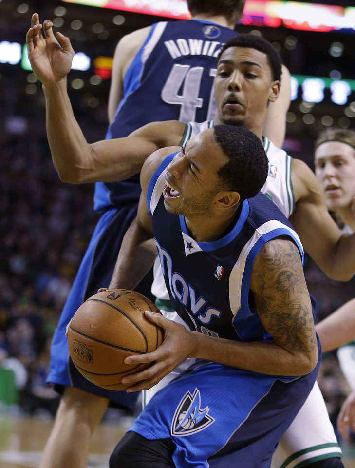 Photo - Dallas Mavericks point guard Devin Harris (20) drives to the hoop as Boston Celtics Boston Celtics point guard Phil Pressey (26) applies defensive pressure during the second half of their NBA basketball game in Boston, Sunday, Feb. 9, 2014. The Mavericks defeated the Celtics 102-91. (AP Photo/Stephan Savoia)