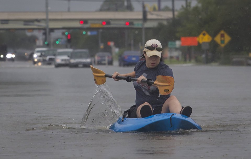Photo - A woman kayaks down a flooded section of FM 518 near the intersection with Interstate 45 in League City, Texas, on Sunday, Aug. 27, 2017.  The remnants of Hurricane Harvey sent devastating floods pouring into Houston Sunday as rising water chased thousands of people to rooftops or higher ground. (Stuart Villanueva/The Galveston County Daily News via AP)