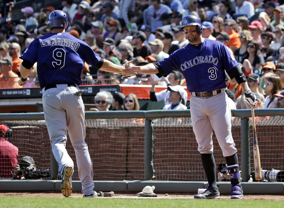 Photo - Colorado Rockies' D.J. LeMahieu, left, is greeted by teammate Michael Cuddyer, right, after scoring on a single by teammate Drew Stubbs during the eighth inning of a baseball game against the San Francisco Giants on Sunday, April 13, 2014, in San Francisco. (AP Photo/Marcio Jose Sanchez)