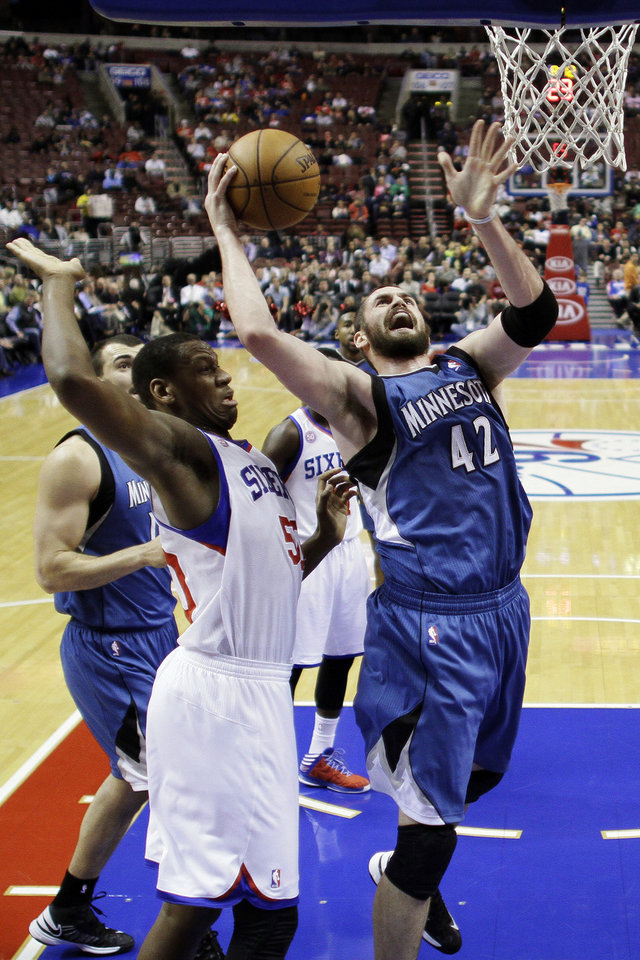 Photo - Minnesota Timberwolves' Kevin Love (42) shoots as Philadelphia 76ers' Lavoy Allen defends in the first half of an NBA basketball game, Tuesday, Dec. 4, 2012, in Philadelphia. (AP Photo/Matt Slocum)