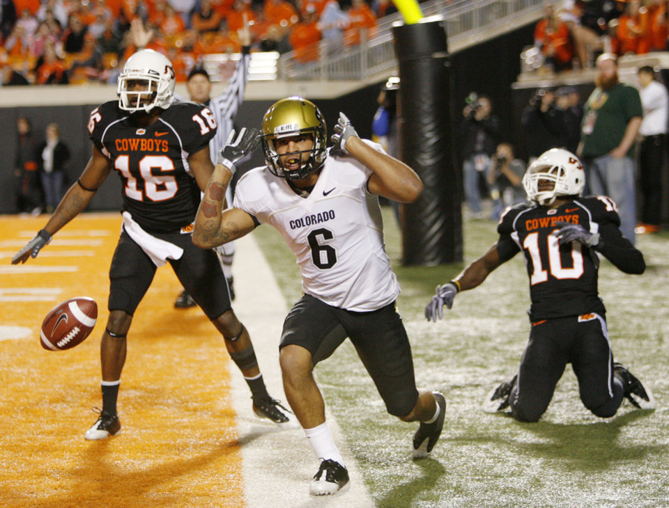 Photo - Colorado's Markques Simas (6) celebrates in front of OSU's Perrish Cox (16) and Markelle Martin (10) after Simas made a touchdown catch in the third quarter during the college football game between Oklahoma State University (OSU) and the University of Colorado (CU) at Boone Pickens Stadium in Stillwater, Okla., Thursday, Nov. 19, 2009. OSU won, 31-28. Photo by Nate Billings, The Oklahoman