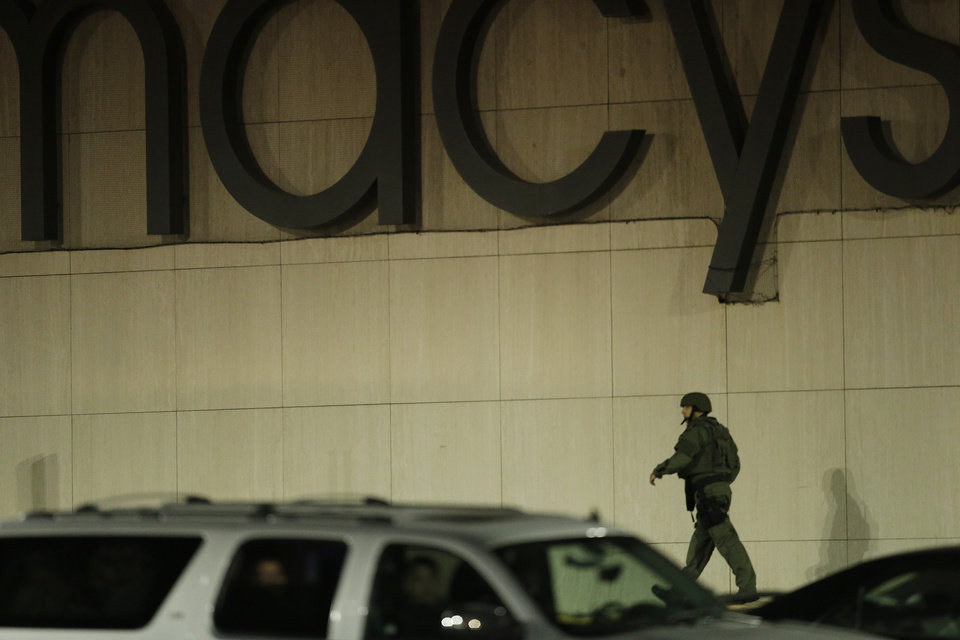 Photo - An official wearing tactical gear walks outside of the Garden State Plaza Mall following reports of a shooter, Monday, Nov. 4, 2013, in Paramus, N.J. Hundreds of law enforcement officers converged on the mall Monday night after witnesses said multiple shots were fired there. (AP Photo/Julio Cortez)