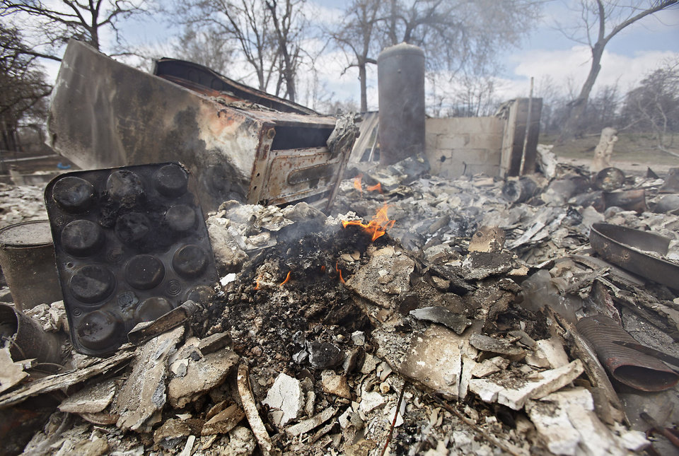 A fire still burn in a home destroyed by wildfires on Friday, April 10, 2009, in Choctaw, Okla.  Photo by Chris Landsberger, The Oklahoman