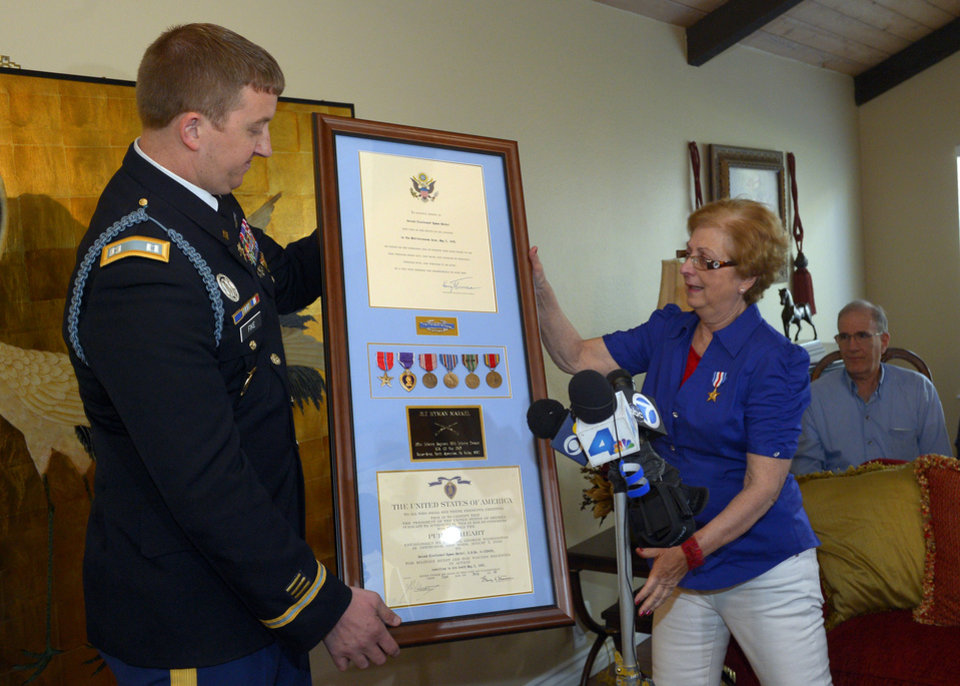 Photo - Army Capt. Zachariah L. Fike presents Hyla Merin with a plaque that contains medals, from left, the Bronze Star, the Purple Heart, the Army Good Conduct Medal, American Campaign Medal, European-African-Middle Eastern Campaign Medal and the World War II Victory Medal along with a Silver Star that he pinned to her during a ceremony at her home, Sunday, Feb. 17, 2013, in Thousand Oaks, Calif. The medals were presented posthumously to her father after they were recently discovered in an apartment where Merin's mother and aunts had once lived. (AP Photo/Mark J. Terrill)