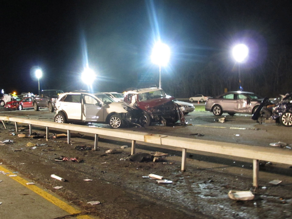 Photo - Damaged vehicles and debris are strewn across the Long Island Expressway following a chain reaction crash on Wednesday, Dec. 19, 2012, in Shirley, N.Y. At least one person was killed and 32 injured. (AP Photo/Frank Eltman)