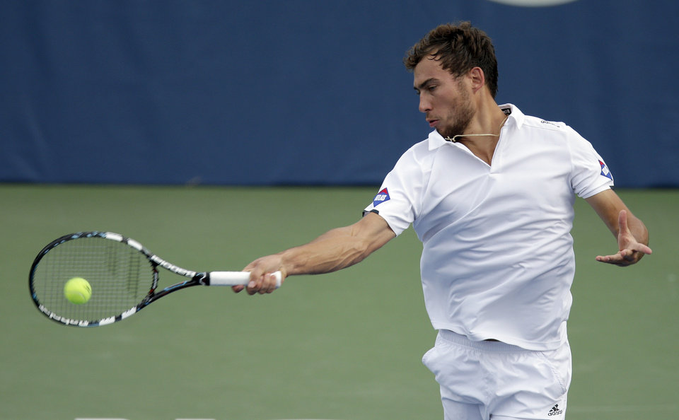 Photo - Jerzy Janowicz, of Poland, returns a shot against Sam Querrey during a semifinal at the Winston-Salem Open tennis tournament in Winston-Salem, N.C., Friday, Aug. 22, 2014. (AP Photo/Chuck Burton)