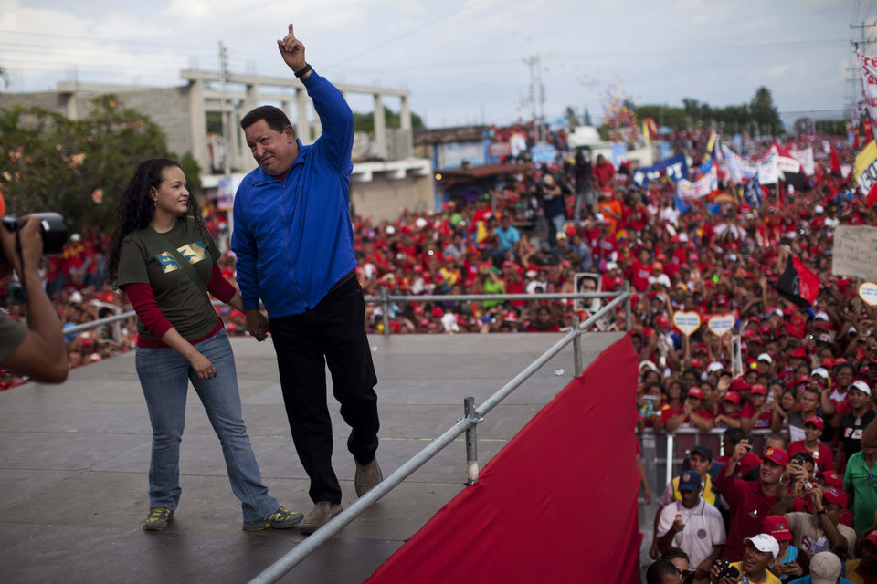 Venezuela's President Hugo Chavez holding hands with his daughter Rosa Virginia, left, gestures to supporters during a campaign rally in Yaracuy, Venezuela, Tuesday, Oct. 2, 2012. Venezuela's presidential election is scheduled for Oct. 7. (AP Photo/Rodrigo Abd)