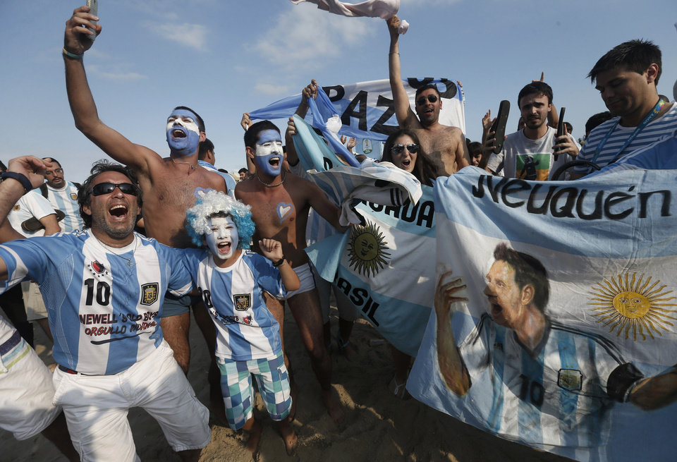 Photo - Argentina soccer fans celebrate their team's victory over Iran after a live telecast of the World Cup match inside the FIFA Fan Fest area on Copacabana beach, in Rio de Janeiro, Brazil, Saturday, June 21, 2014. Argentina won 1-0. (AP Photo/Silvia Izquierdo)