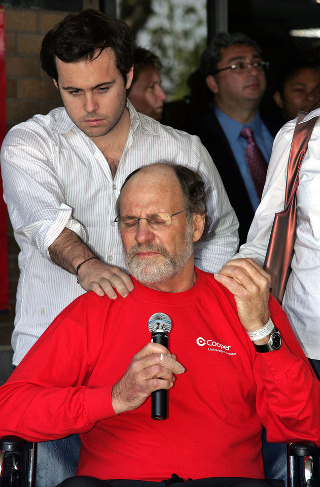 Photo - FILE - In this April 30, 2007, file photo, Jeffrey Corzine, left, rests his hand on his father's shoulder as New Jersey Gov. Jon S. Corzine pauses after being released from Cooper University Hospital in Camden, N.J. On Thursday, March 13, 2014, a spokesman for Jon Corzine stated that Jeffrey Corzine has died at age 31. Details regarding the cause of death were not immediately known. (AP Photo/Mel Evans, File)