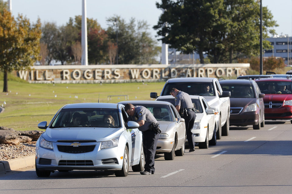 Photo - Oklahoma City police officers gather information from vehicles leaving Will Rogers World Airport, Tuesday November, 15 2016. The airport was put on lockdown after a shooting in the main terminal. Photo By Steve Gooch, The Oklahoman