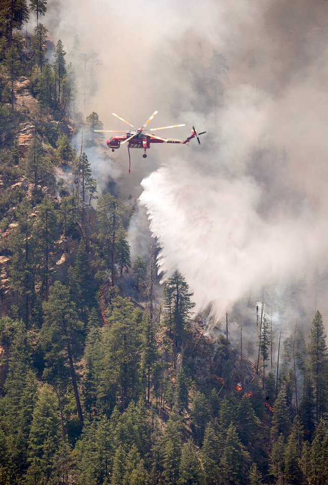 Photo - Helicopters drop water on part of the Slide Fire in Sterling Canyon at the Oak Creek Overlook above Sedona, Ariz. on Thursday, May 22, 2014. Hundreds of firefighters worked Thursday to protect communities on the edge of Flagstaff from a wildfire that is chewing up a scenic Arizona canyon with towering flames and burning entire trees down to nothing but ash. (AP Photo/The Arizona Republic, Michael Schennum)  MARICOPA COUNTY OUT; MAGS OUT; NO SALES
