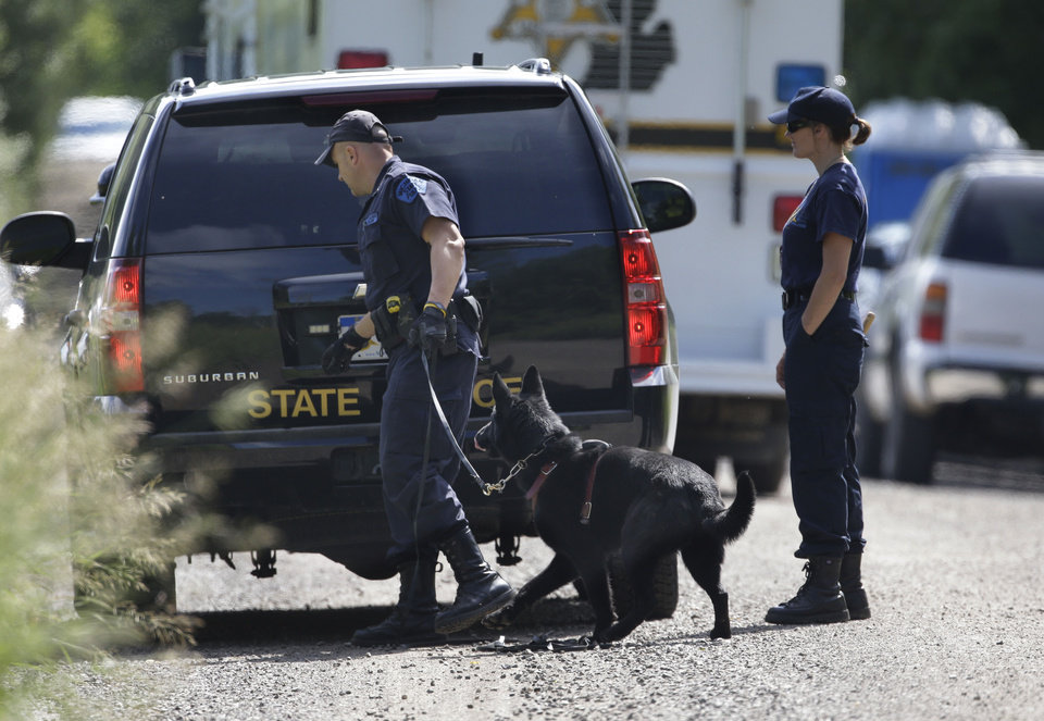 Photo - Law enforcement officials from the Michigan State Police help search the area in Oakland Township, Mich., Tuesday, June 18, 2013 where officials continue the search for the remains of Teamsters union president Jimmy Hoffa who disappeared from a Detroit-area restaurant in 1975. (AP Photo/Carlos Osorio)
