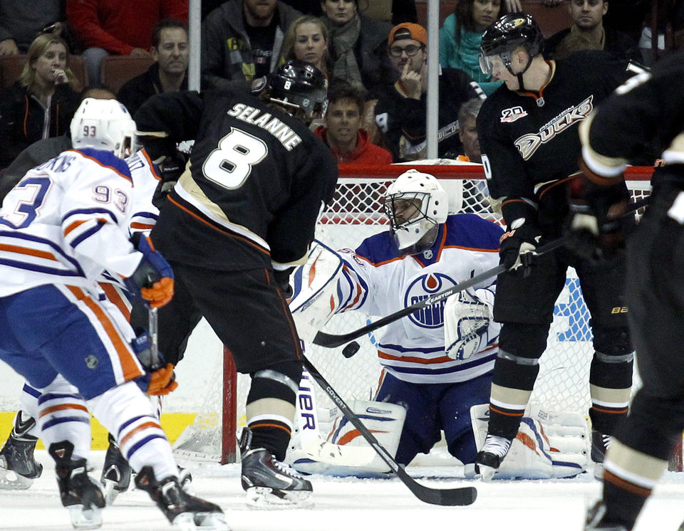 Photo - Edmonton Oilers goalie Ilya Bryzgalov, center, of Russia, stops a defection by Anaheim Ducks right wing Corey Perry, right, with right wing Teemu Selanne (8), of Finland, looking for the rebound during the first period of an NHL hockey game, Friday, Jan. 3, 2014, in Los Angeles.  (AP Photo/Alex Gallardo)