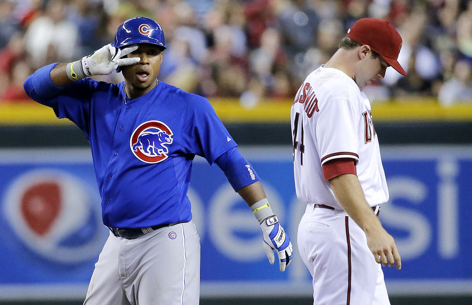 Photo - Chicago Cubs' Luis Valbuena, left, gestures to his bench after hitting a standup double during the fourth inning of a baseball game as Arizona Diamondbacks Paul Goldschmidt looks away, Friday, July 18, 2014, in Phoenix. (AP Photo/Matt York)