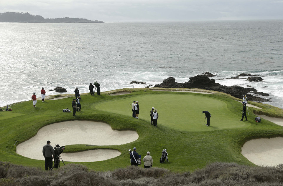 Photo - Phil Mickelson putts on the seventh green of the Pebble Beach Golf Links during the second round of the AT&T Pebble Beach Pro-Am golf tournament on Friday, Feb. 7, 2014, in Pebble Beach, Calif. (AP Photo/Eric Risberg)