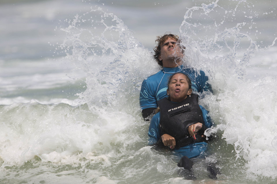 Photo - In this March 16, 2013 photo, Monique Oliveira is aided by an AdaptSurf volunteer as a wave breaks at Barra da Tijuca beach in Rio de Janeiro, Brazil. AdaptSurf is a Rio-based non-governmental organization that aims to make beaches accessible to the disabled and encourage them to practice water sports. The organization is the first of its kind in Brazil. (AP Photo/Felipe Dana)