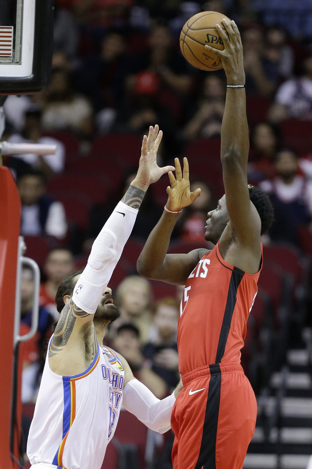 Photo - Houston Rockets center Clint Capela, right, shoots over Oklahoma City Thunder center Steven Adams during the first half of an NBA basketball game, Monday, Oct. 28, 2019, in Houston. (AP Photo/Eric Christian Smith)