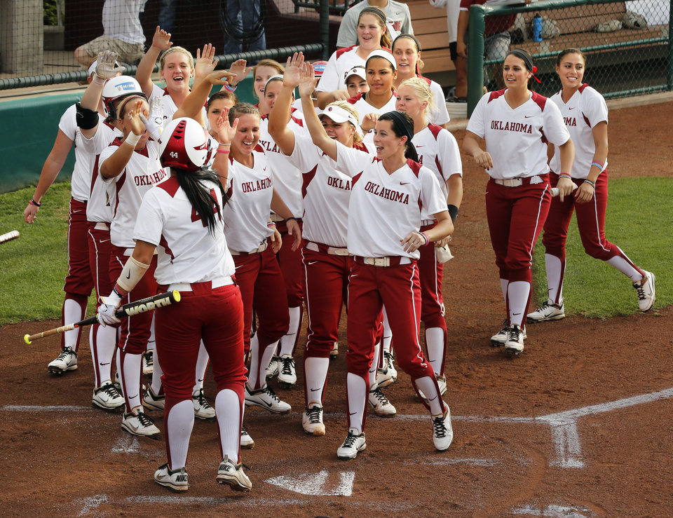 Photo - Sooner Lauren Chamberlain is created by the team after slideing home safe under the tag of Meagan May in NCAA Super Regional softball as the University of Oklahoma (OU) Sooners defeats Texas A&M 10-2 at Marita Hines Field on Friday, May 24, 2013 in Norman, Okla. Photo by Steve Sisney, The Oklahoman