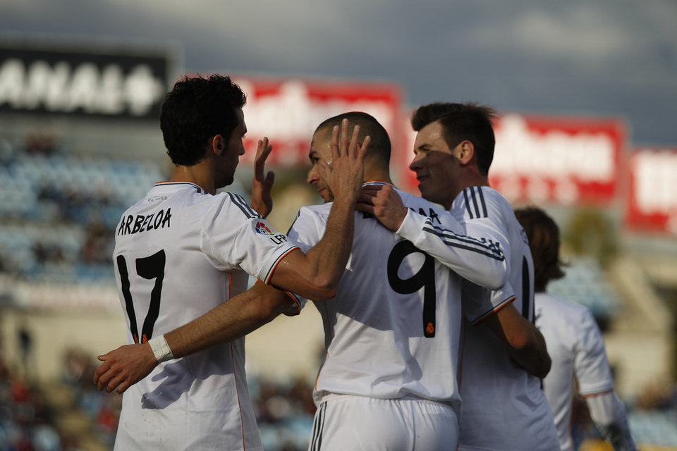 Photo - Real's Karim Benzema, center, celebrates his goal with teammates during a Spanish La Liga soccer match between Real Madrid and Getafe at the Coliseum Alfonso Perez stadium in Madrid, Spain, Sunday, Feb. 16, 2014. (AP Photo/Gabriel Pecot)