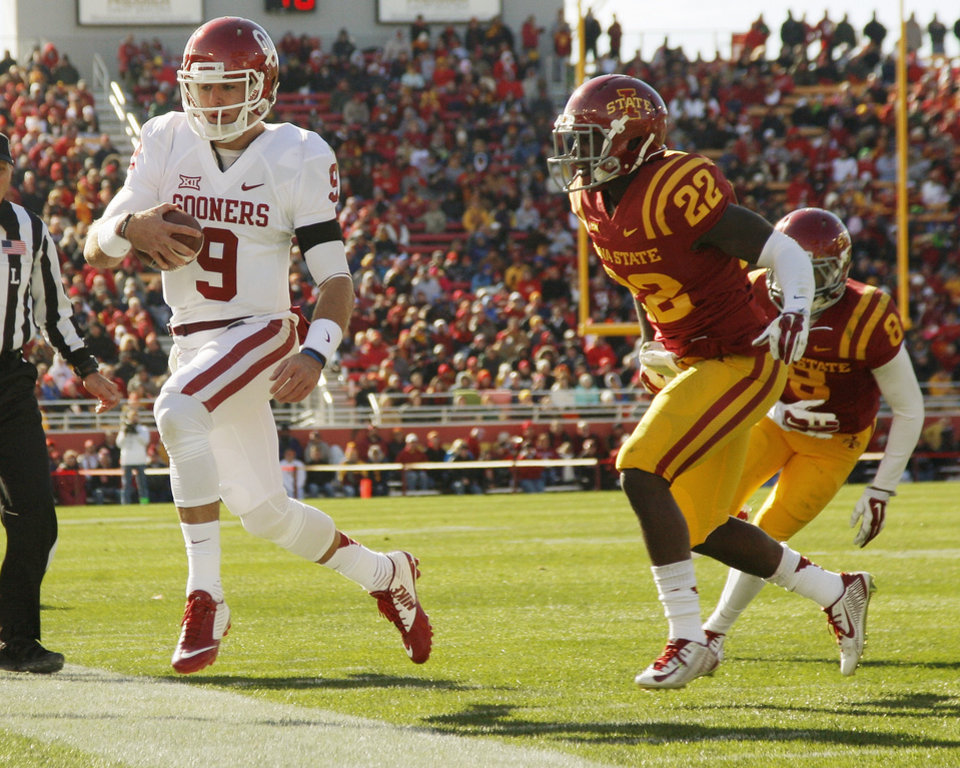 Photo - Oklahoma's Trevor Knight (9) runs out of bounds as he is pursued by Iowa State's T.J. Mutcherson (22) and Kenneth Lynn (8) during a college football game between the University of Oklahoma Sooners (OU) and the Iowa State Cyclones (ISU) at Jack Trice Stadium in Ames, Iowa, Saturday, Nov. 1, 2014. Photo by Nate Billings, The Oklahoman