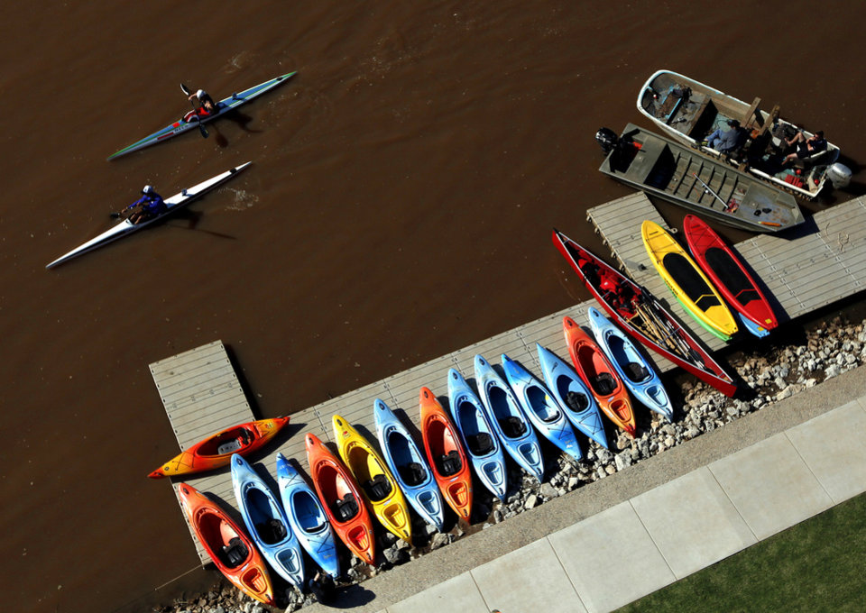 Competitors paddle pass boats lend up on the shore line during races for the USA Canoe/Kayak World Cup Team Trials on the Oklahoma River,  Saturday, April 21, 2012. Photo by Sarah Phipps, The Oklahoman.