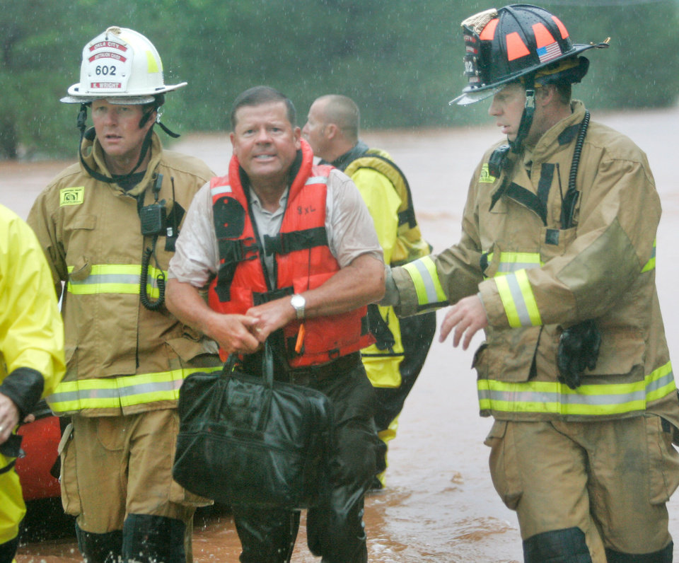 Photo - Oklahoma City firefighters rescued stranded motorist Randy Robinson from  a bridge near Hefner road and Sooner in Oklahoma City, Oklahoma June 14 , 2010. Photo by Steve Gooch, The Oklahoman