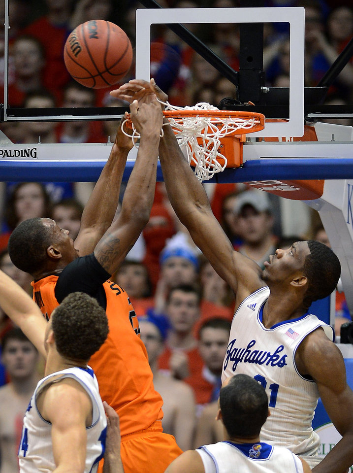 Photo - Kansas' Joel Embiid, top right, rejects a shot by Oklahoma State's Kamari Murphy during the first half at Allen Fieldhouse in Lawrence, Kan., on Saturday, Jan. 18, 2014. (Rich Sugg/Kansas City Star/MCT)