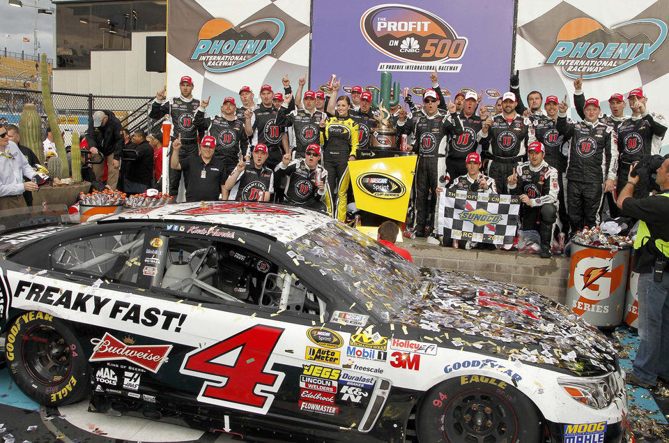 Photo - Kevin Harvick, standing to the right of the winner's trophy, joins his crew in posing for photographers in Victory Lane after winning the NASCAR Sprint Cup Series auto race Sunday, March 2, 2014, in Avondale, Ariz. (AP Photo/Ross D. Franklin)