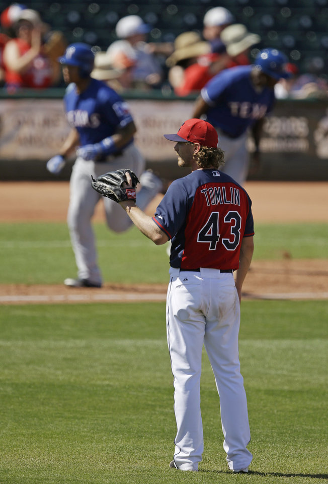 Photo - Cleveland Indians' Josh Tomlin gets a new baseball after Texas Rangers' Michael Choice hit a two-run home run during the sixth inning of a spring exhibition baseball game Tuesday, March 25, 2014, in Goodyear, Ariz. (AP Photo/Darron Cummings)
