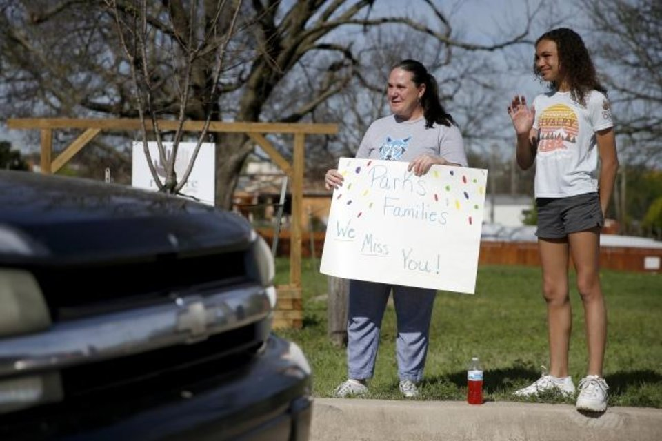 Photo -  Teacher Shannon Dragoo and her daughter Nayeli Dragoo-Crawford , 10, greet people Thursday as they line up for a drive-thru food distribution held by Restore OKC in partnership with Skyline Urban Ministry. [Bryan Terry/The Oklahoman]