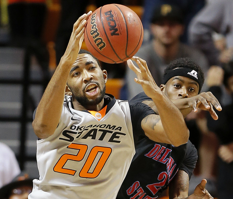 Photo - Oklahoma State's Michael Cobbins reaches for a rebound beside Delaware State's Kendal Williams (2) during an NCAA college basketball between Oklahoma State University and Delaware State at Gallagher-Iba Arena in Stillwater, Okla., Tuesday, December 17, 2013. Photo by Bryan Terry, The Oklahoman