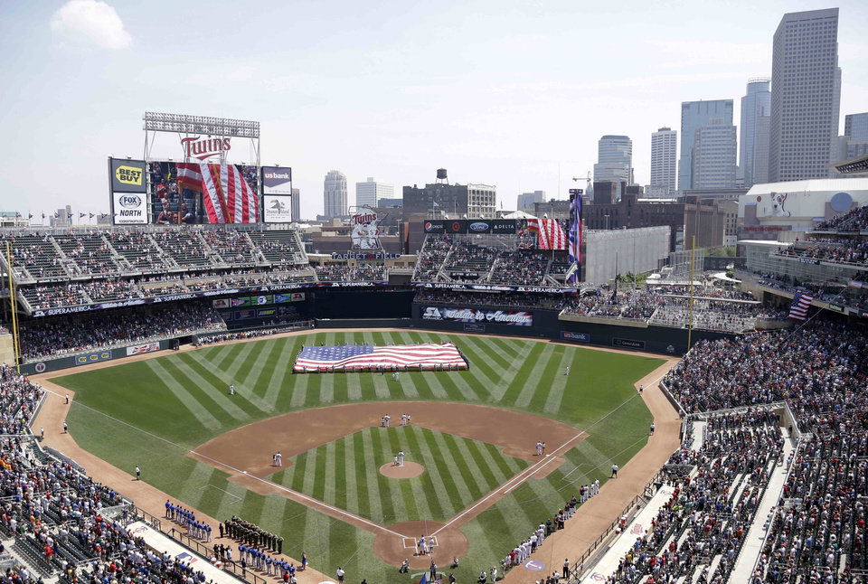 Photo - FILE - In this June 30, 2013 file photo, members of the Armed Forces hold a large flag at Target field in Minneapolis where the Minnesota Twins hosted Armed Forces Appreciation Day prior to the baseball game between the Twins and the Kansas City Royals. Major League Baseball's All Star festivities will be held in the 4-year-old ballpark, the one that helped outdoor baseball make a return to chilly Minnesota. (AP Photo/Jim Mone, File)