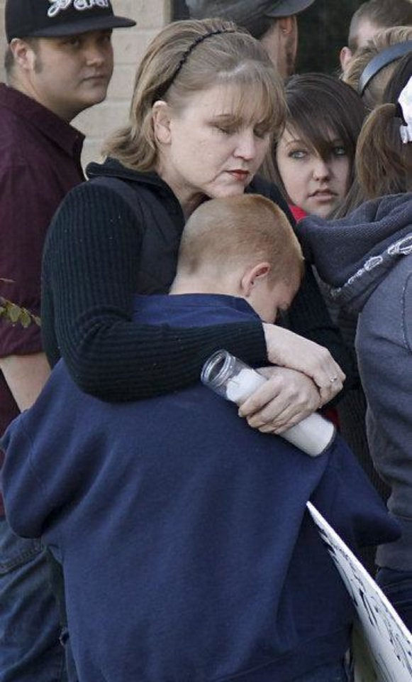 DeAnn Hartman hugs her son Jacob as they gather during a vigil on Tuesday afternoon for Carina Saunders, whose body was found in a duffel bag last week behind a Bethany Homeland last week. <strong>CHRIS LANDSBERGER - CHRIS LANDSBERGER</strong>