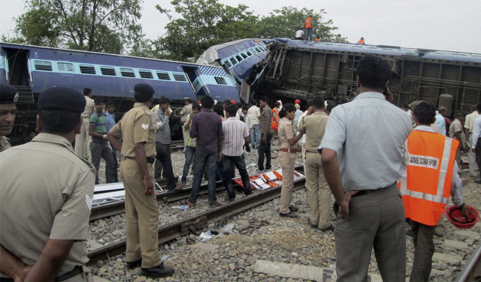 Photo - Indian officials and rescuers stand near the wreckage after the Gorakhpur Express passenger train slammed into a parked freight train Chureb, near Basti, Uttar Pradesh state,, India, Monday, May 26, 2014. According to officials dozens were killed. (AP Photo)