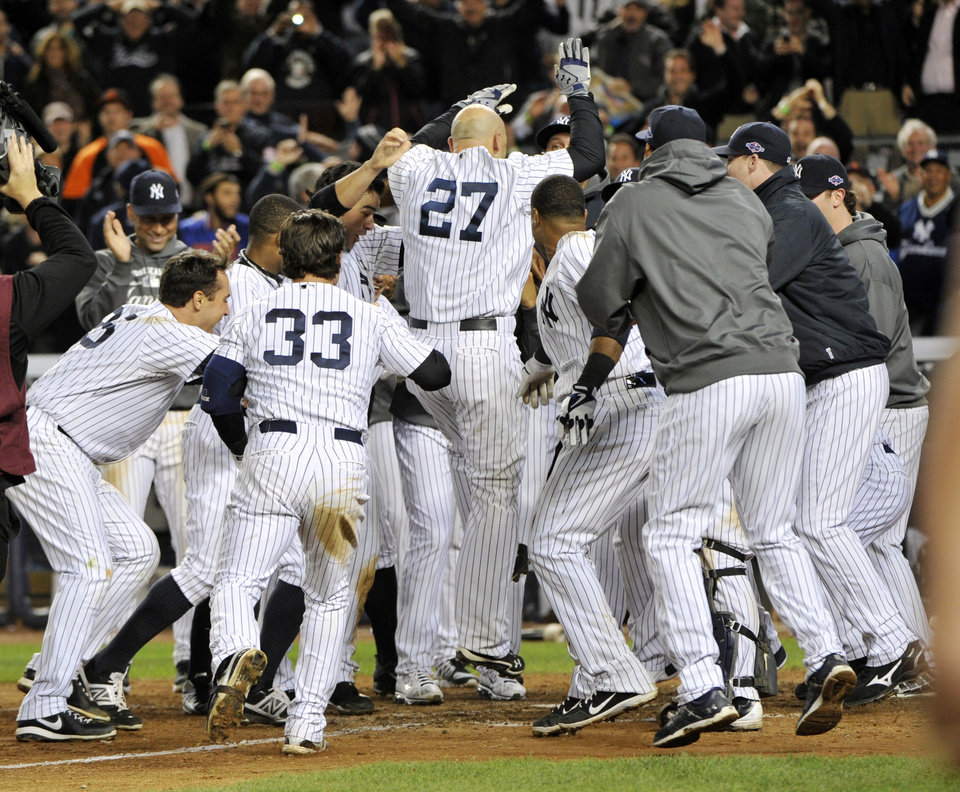 Photo -   New York Yankees' Raul Ibanez (27) celebrates with teammates as he reaches home plate after hitting the game-winning home run during the 12th inning of Game 3 of the American League division baseball series against the Baltimore Orioles on Wednesday, Oct. 10, 2012, in New York. The Yankees won 3-2. (AP Photo/Bill Kostroun)