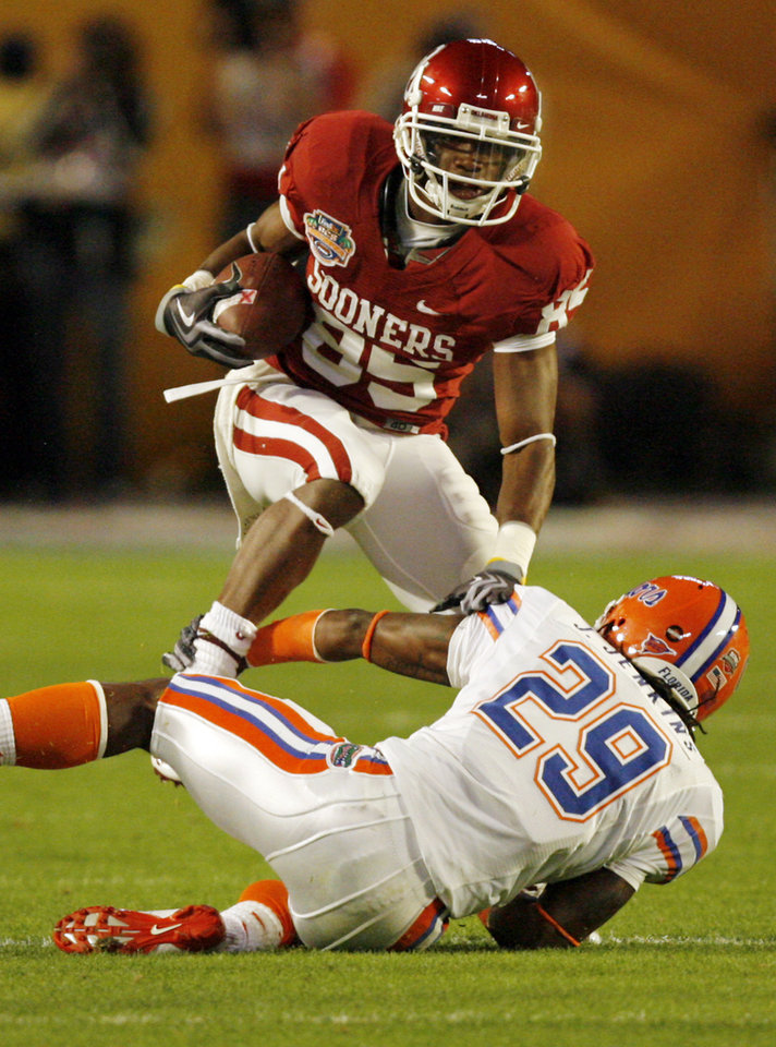 Photo - Oklahoma's Ryan Broyles (85) is brought down by Florida's Janoris Jenkins (29) during the first half of the BCS National Championship college football game between the University of Oklahoma Sooners (OU) and the University of Florida Gators (UF) on Thursday, Jan. 8, 2009, at Dolphin Stadium in Miami Gardens, Fla. PHOTO BY CHRIS LANDSBERGER, THE OKLAHOMAN