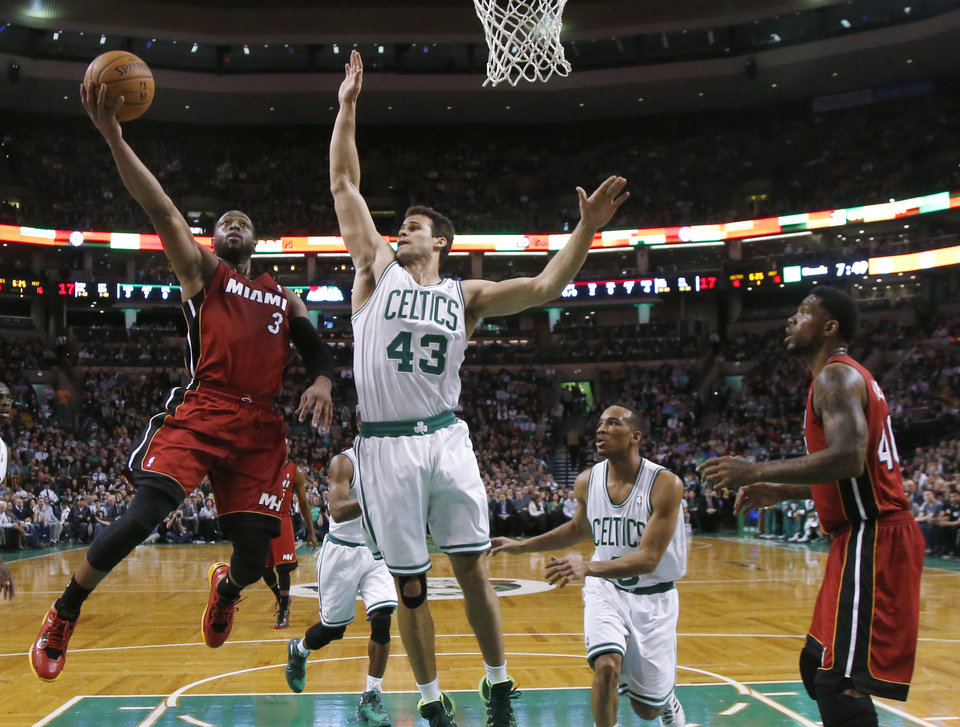 Photo - Miami Heat guard Dwyane Wade (3) drives to the basket against Boston Celtics center Kris Humphries (43) as Celtics guard Avery Bradley (0) and Heat forward Udonis Haslem (40) watch in the first quarter of an NBA basketball game in Boston Wednesday, March 19, 2014. (AP Photo/Elise Amendola)