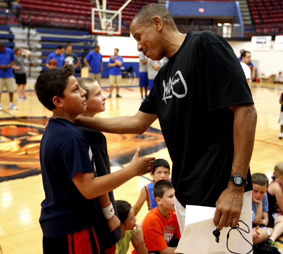 Photo - Otis Birdsong, right, talks with Jeremiah Dobbs, left, and Michael Miller, Plaza Towers fifth graders, as former NBA All-Stars host a basketball clinic for tornado victims on Thursday, June 13, 2013 in Moore, Okla.  Photo by Steve Sisney, The Oklahoman