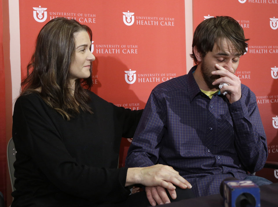 Avalanche survivor, Elisabeth Malloy looks on as skiing partner and initial rescuer Adam Morrey tears up as he discusses their avalanche ordeal during a news conference at the University of Utah Health Care's Burn Center Wednesday, Jan. 16, 2013, in Salt Lake City. Malloy suffered frost bite in her toes and fingers, but emerged otherwise unscathed from Saturday�s near-death encounter in the mountains east of Salt Lake City. She survived thanks to her boyfriend, Adam Morrey, avalanche rescue beacons, a skier that wandered by and avalanche rescue teams.  (AP Photo/Rick Bowmer)
