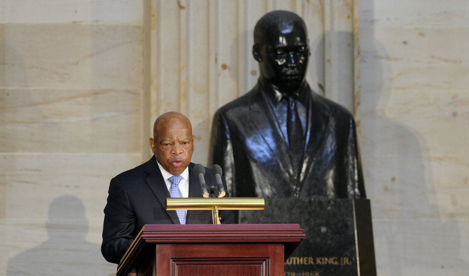 Photo - Rep. John Lewis, D-Ga., stands in front of a statue of Dr. Martin Luther King, Jr., as he speaks during a 50th anniversary ceremony for the Civil Rights Act of 1964, Tuesday, June 24, 2014, in the Capitol Rotunda on Capitol Hill in Washington. A Congressional Gold Medal in honor of Dr. and Mrs. Martin Luther King, Jr., who were instrumental in the law's passage, was also presented. (AP Photo/Susan Walsh)