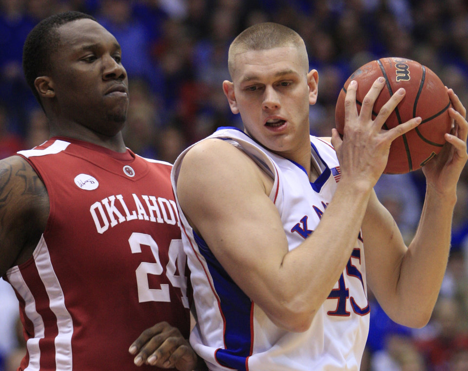Photo - UNIVERSITY OF OKLAHOMA, OU: Kansas center Cole Aldrich (45) works against Oklahoma forward Tiny Gallon (24) during the first half of an NCAA college basketball game Monday, Feb. 22, 2010, in Lawrence, Kan. (AP Photo/Orlin Wagner) ORG XMIT: KSOW108