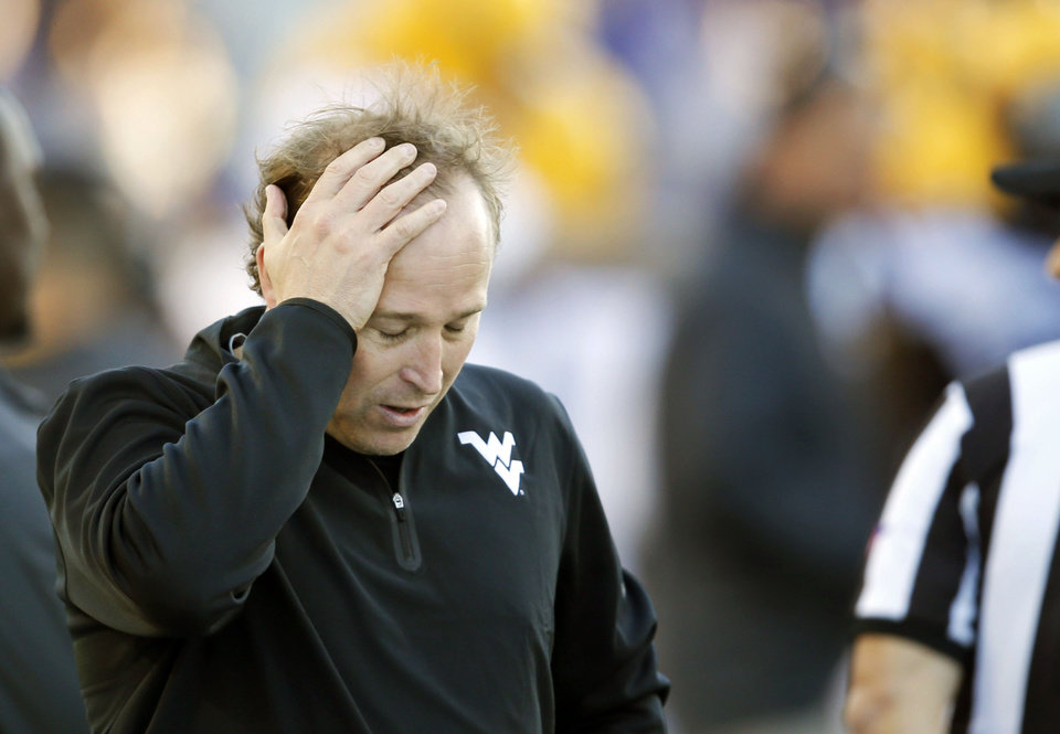 Photo - FILE - In this Oct. 26, 2013, file photo, West Virginia coach Dana Holgorsen holds his head during the second half of an NCAA college football game against Kansas State in Manhattan, Kan. Holgorsen needs no reminder about the lack of success he's seen on the field since ushering in West Virginia's move to the Big 12. (AP Photo/Orlin Wagner, File)