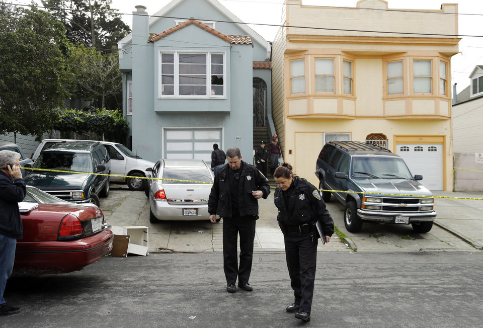Photo - San Francisco police officers search for evidence and guard the home of a woman who was set on fire Sunday, Jan. 6, 2013, in San Francisco. San Francisco police say a woman is hospitalized with what are being described as