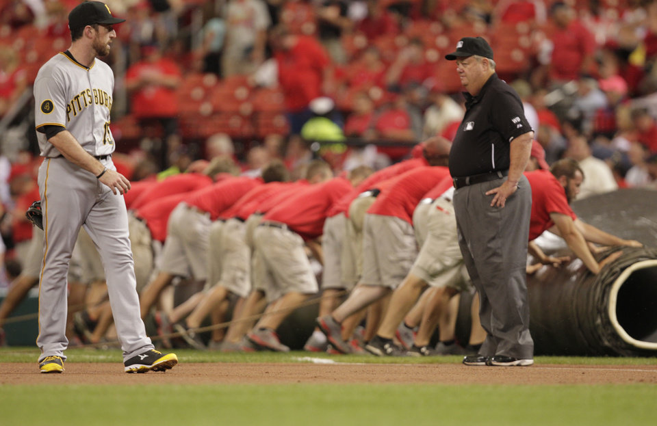 Photo - Pittsburgh Pirates first baseman Ike Davis (15) and umpire Joe West look on as the St. Louis Cardinals grounds crew pulls the tarp in the first inning of a baseball game, Monday, July 7, 2014 in St. Louis. (AP Photo/Tom Gannam)