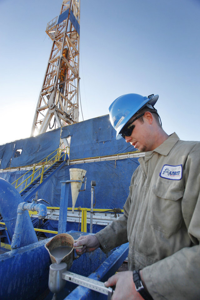 Photo - Derrickman Ryan Frayne works on mixing drilling mud at a SandRidge oil drilling rig near Medford. Photo By David McDaniel, The Oklahoman  David McDaniel