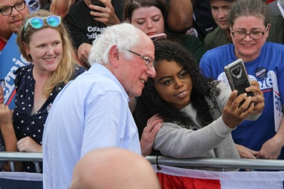 Photo -  Bernie Sanders pauses for a selfie Saturday in Norman's Reaves Park. The Democratic presidential candidate was in Norman for a political rally. [Paxson Haws/The Oklahoman]