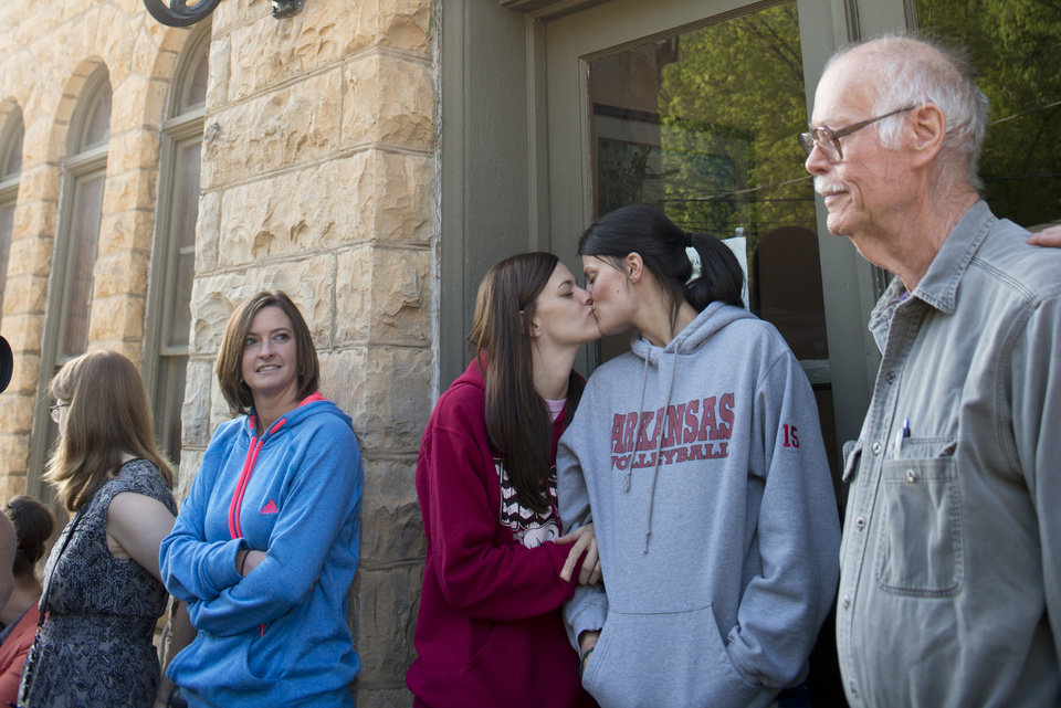 Photo - Jennifer Rambo, left, of Jacksonville, Ark., kisses her partner Kristin Seaton, right, of Fort Smith, Ark., as they wait in line at the Carroll County Courthouse to apply for a marriage license, Saturday, May 10, 2014, in Eureka Springs, Ark. Rambo and Seaton drove to Eureka Springs Friday night and slept in their car after a judge overturned Ammendment 83, which banned same-sex marriage in the state of Arkansas. (AP Photo/Sarah Bentham)