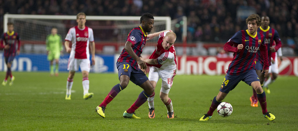 Photo - Ajax's Davey Klaassen, centre right, clashes with Barcelona's Alex Song, centre left, during the Group H Champions League soccer match between Ajax and FC Barcelona at the ArenA stadium in Amsterdam, Netherlands, Tuesday Nov. 26, 2013. (AP Photo/Patrick Post)